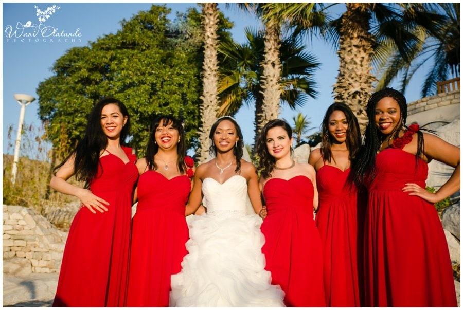 beautiful nigerian bridesmaids in red cocktail dresses at outdoor dubai wedding