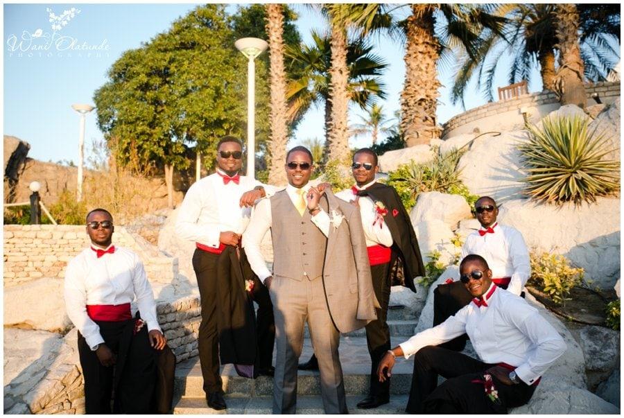 nigerian groomsmen in bow ties and red at outdoor nigerian wedding